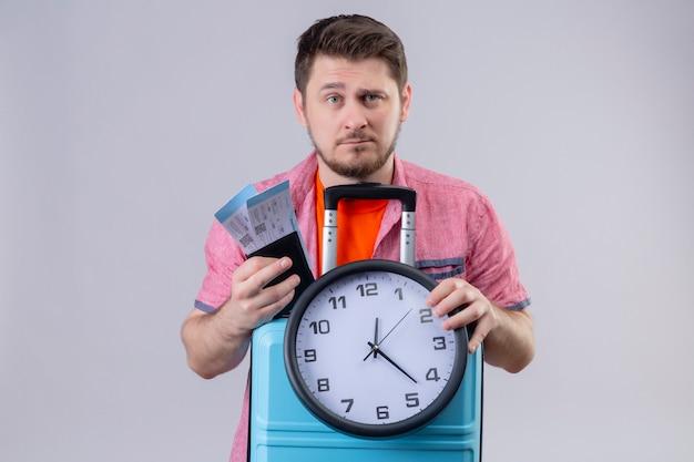 Uomo giovane viaggiatore in possesso di biglietti aerei e valigia con orologio che guarda l'obbiettivo con seria espressione fiduciosa sul viso in piedi su sfondo bianco isolato