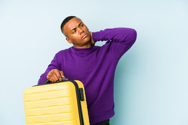 Uomo giovane viaggiatore in possesso di una valigia toccando il dorso della testa, pensando e facendo una scelta.