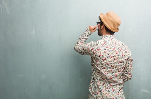 Uomo giovane viaggiatore indossa una camicia colorata mostrando indietro, in posa e in attesa, guardando indietro