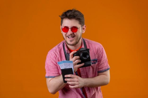 Uomo giovane viaggiatore indossando occhiali da sole con fotocamera in possesso di biglietti aerei che guarda l'obbiettivo felice ed è uscito sorridendo allegramente in piedi su sfondo arancione