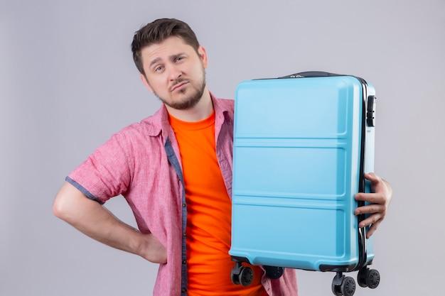 Uomo giovane viaggiatore scontento che tiene la valigia blu con l'espressione scettica sul viso in piedi sopra il muro bianco