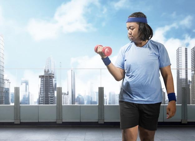 Uomo grasso asiatico che fa esercizio con manubri