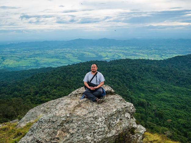 Uomo grasso asiatico seduto su una scogliera rocciosa e meditazione sulla montagna di khao luang nel parco nazionale di ramkhamhaeng, provincia di sukhothai thailandia