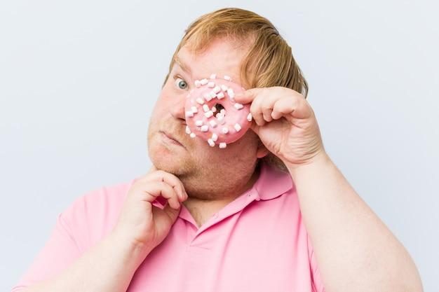 Uomo grasso biondo pazzo caucasico che tiene le ciambelle
