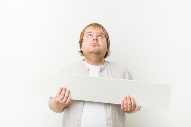 Uomo grasso biondo pazzo caucasico con un cartello