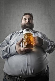 Uomo grasso che mangia una birra