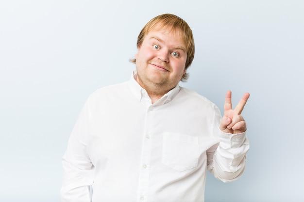 Uomo grasso della giovane testarossa autentica che mostra il segno di vittoria e che sorride largamente.