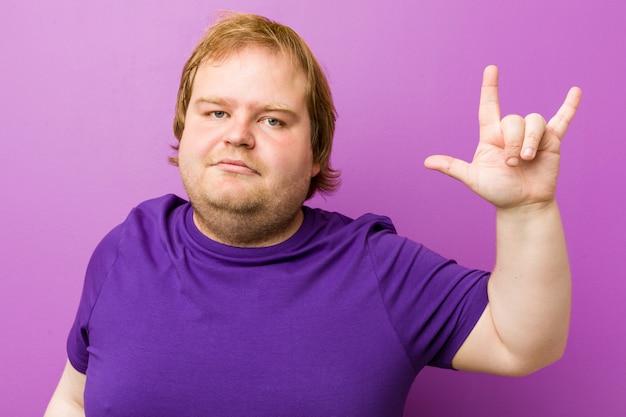 Uomo grasso di giovane rossa autentica che mostra un gesto di corna