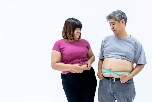 Uomo grasso e donna che esaminano a vicenda il grasso della pancia