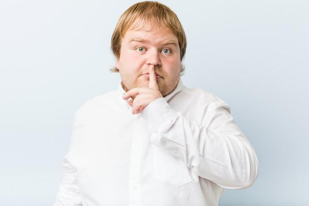 Uomo grasso giovane autentico rossa mantenendo un segreto o chiedendo silenzio.