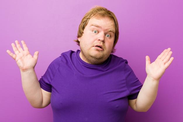 Uomo grasso giovane autentico rossa sorpreso e scioccato.