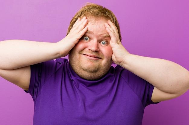 Uomo grasso giovane rossa autentica ride con gioia tenendo le mani sulla testa. felicità .