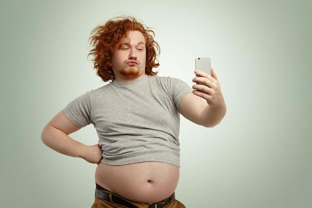 Uomo grassoccio in sovrappeso divertente con le labbra di anatra che indossa la maglietta sottodimensionata con la pancia che pende dai pantaloni