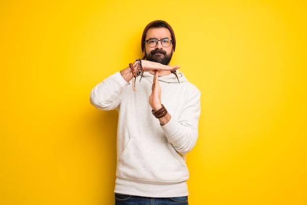 Uomo hippie con i dreadlocks che fa fermare il gesto con la mano per fermare un atto