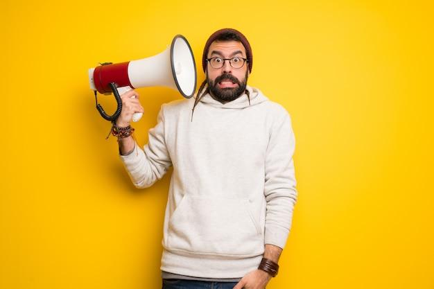 Uomo hippie con i dreadlocks che prende un megafono che fa molto rumore