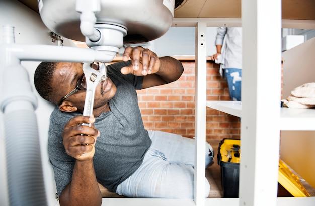 Uomo idraulico che fissa il lavello della cucina