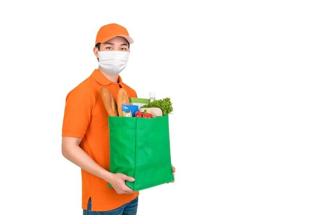 Uomo igienico che indossa il sacchetto della spesa di trasporto della drogheria del supermercato della maschera medica che offre servizio di consegna a domicilio isolato nel bianco