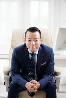 Uomo in abbigliamento formale chinandosi in avanti nella sua poltrona da ufficio con le dita incrociate