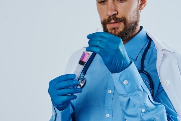 Uomo in abbigliamento medico che lavora come assistente di laboratorio con liquido in boccetta