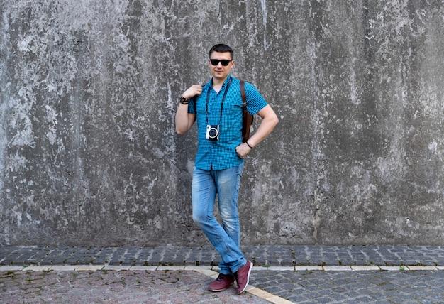 Uomo in abiti casual con fotocamera e zaino