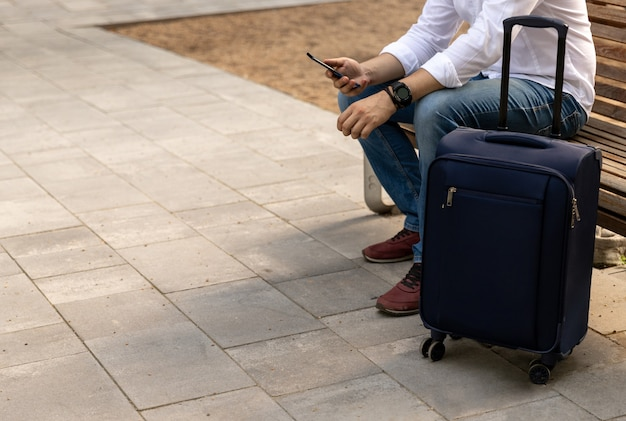 Uomo in abiti casual, seduto su una panchina con un bagaglio