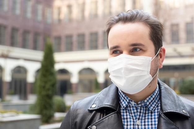 Uomo in abiti eleganti per la strada con una maschera medica, scoppio della malattia virale coronavirus covid-2019