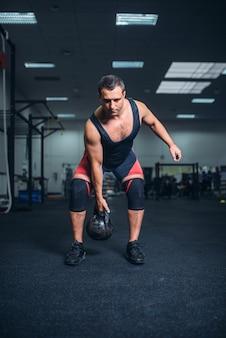 Uomo in abiti sportivi facendo esercizio con kettlebell