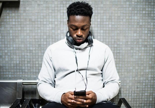 Uomo in attesa che manda un sms sul suo telefono