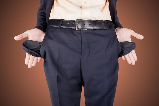 Uomo in bancarotta che mostra le tasche vuote