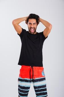 Uomo in beachwear urlando con le mani dietro la testa
