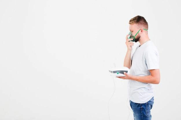 Uomo in bianco con nebulizzatore per l'asma