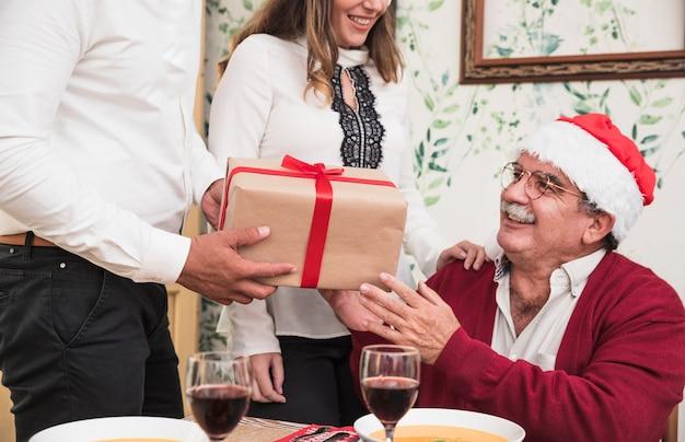 Uomo in bianco dando scatola regalo al vecchio uomo in cappello di babbo natale