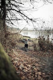 Uomo in buona salute del ciclista che porta la sua bicicletta sulla sua parte posteriore che cammina sulla traccia della foresta