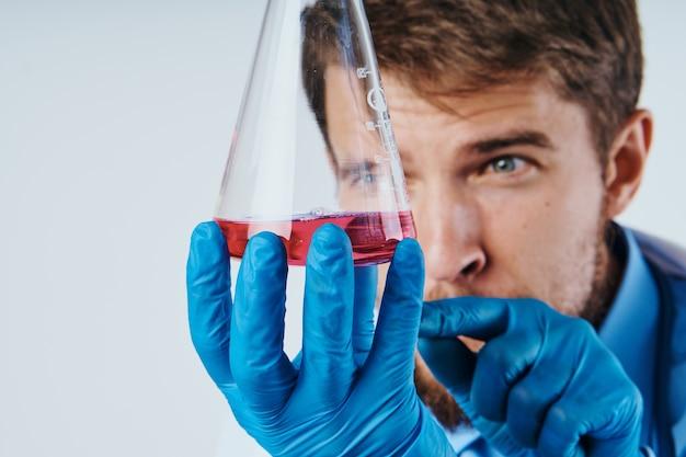 Uomo in camice medico assistente di laboratorio con liquido in boccetta e medico stetoscopio