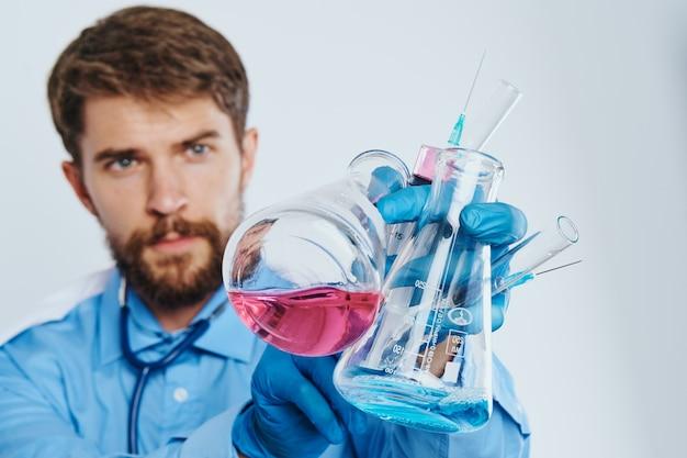 Uomo in camice medico assistente di laboratorio con liquido in pallone e luce di reazione chimica medico stetoscopio