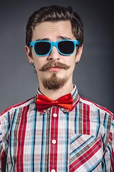 Uomo in camicia a quadri e farfallino con gli occhiali in studio