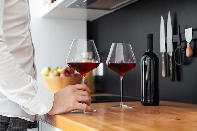 Uomo in camicia bianca, bicchiere di borgogna con vino rosso, bottiglia sul ripiano del tavolo in legno della cucina