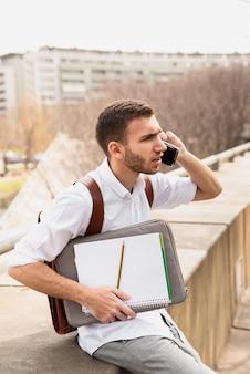 Uomo in camicia bianca che parla sul telefono e che osserva via