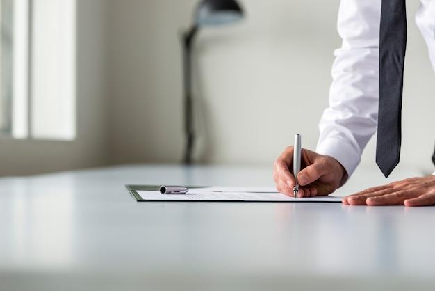 Uomo in camicia bianca firma contratto o modulo di iscrizione
