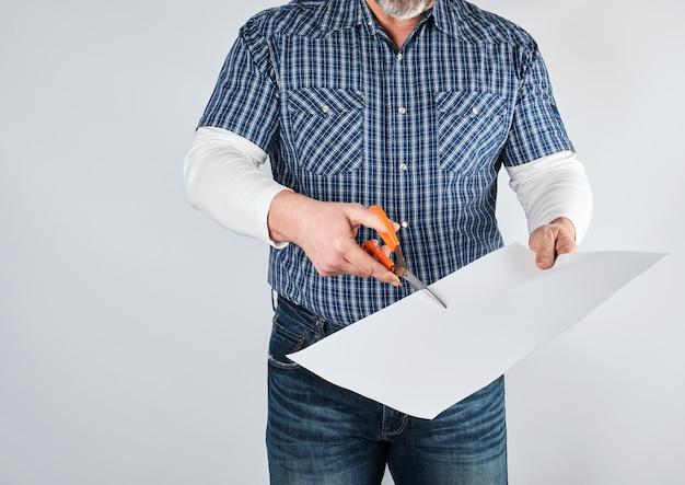 Uomo in camicia blu forbici foglio di carta bianca