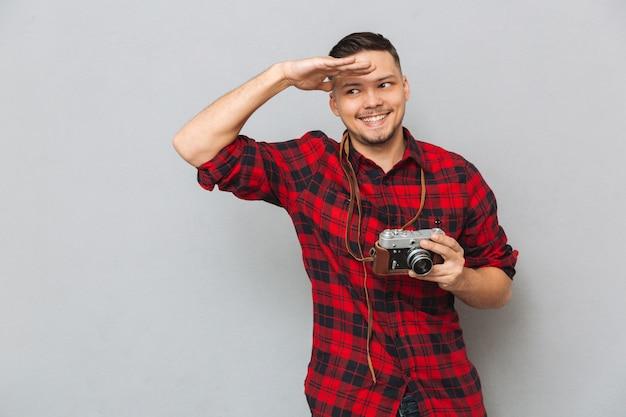 Uomo in camicia che tiene la retro macchina fotografica e che esamina macchina fotografica