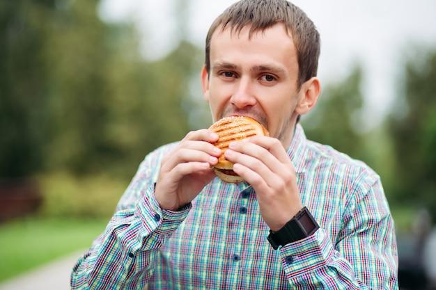 Uomo in camicia controllata che mangia hamburger saporito all'aperto.