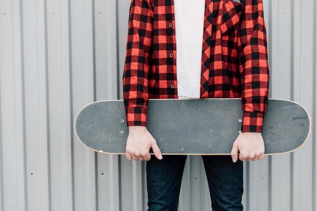 Uomo in camicia di flanella che tiene skateboard