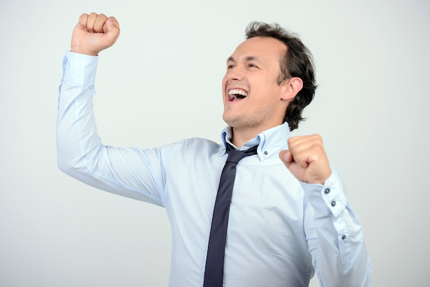 Uomo in camicia e cravatta che gesturing mentre in piedi contro.