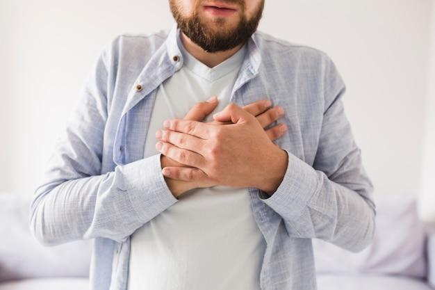 Uomo in camicia grigia che ha mal di cuore