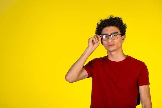 Uomo in camicia rossa che tocca i suoi occhiali e flirtare