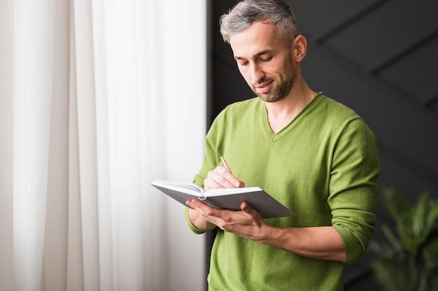 Uomo in camicia verde che esamina il suo taccuino
