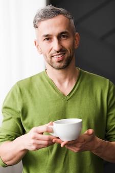 Uomo in camicia verde che tiene una tazza di caffè bianca