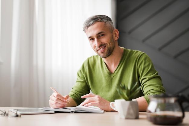 Uomo in camicia verde seduto alla sua scrivania