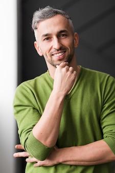 Uomo in camicia verde sorridente fiducioso